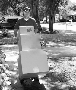 6002253-delivery-man-or-mover-pushing-a-dolly-loaded-with-boxes-up-the-front-walk